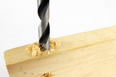 Drilling holes with a wood drill in a workshop. Joinery works performed with the use of cutting tools. White background. Stok Fotoğraf
