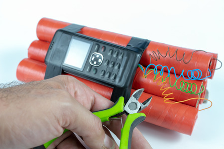Dynamite sticks with time igniter. Explosive material with ignition connected to a mobile phone. White background.