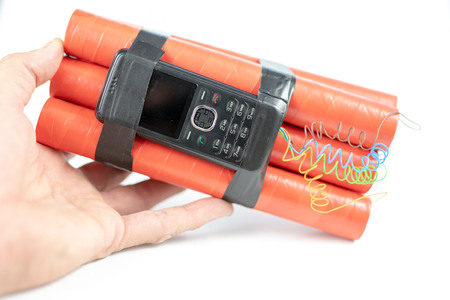 Dynamite sticks with time igniter. Explosive material with ignition connected to a mobile phone. White background. Stock Photo