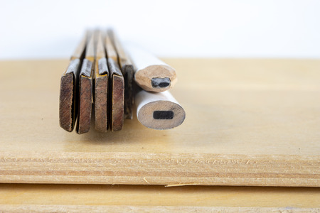 Carpenter's measure and pencil on a workshop table. Measurement of material in the woodworking shop. White background. Stockfoto