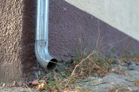 Gutter draining rainwater. The building is equipped with drainage of rainwater from the roof. Season of the summer.