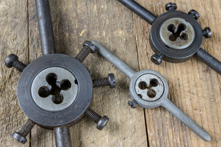 Metalwork tools on the workshop table. Threading dies and taps in an old dusty workshop. Black background.