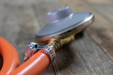 Regler für Propan-Butan-Gasflasche und Zubehör auf einem hölzernen Werkstatttisch. Gaszubehör in der Werkstatt. Dunkler Hintergrund. Standard-Bild