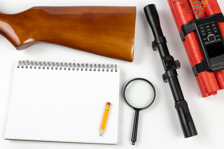A notepad for making notes and a pencil on a table with a firearm. Shooting accessories and materials for quotation. White background.