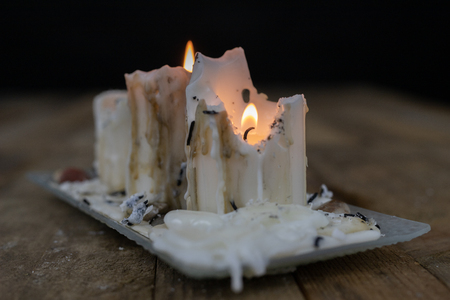 Old candles with dirty wax on a wooden table. Burning dirty candlesticks on a glass stand. Dark background.