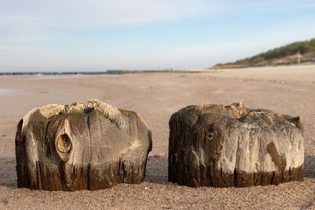 Old breakwater bollards on the sea beach. Coast in central europe. Season of the autumn. Standard-Bild - 112527446
