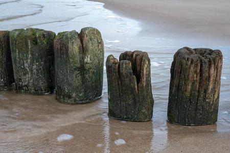 Old breakwater bollards on the sea beach. Coast in central europe. Season of the autumn. Standard-Bild - 112527601