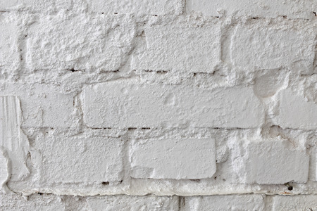 White brick wall. An old brick wall painted with paint and supplemented with plaster. Light background.