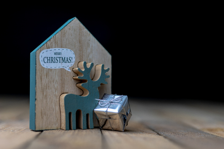 Christmas decorations on the kitchen table. Wooden Christmas figurines prepared for decorating a tree. Dark background.