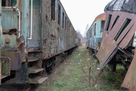 Old destroyed railway wagons. Forgotten railway station in central europe. Season of the autumn.