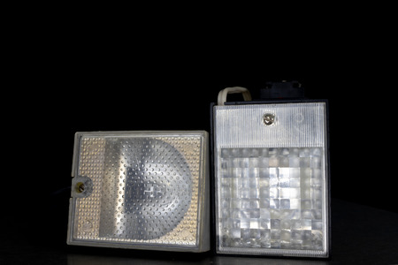 Old flash lamps on a metal table. Photo accessories from central europe. Dark background. Standard-Bild