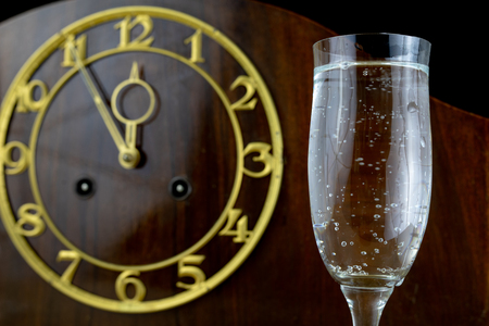 An old clock and glasses full of champagne on New Year's Eve. Five minutes to the new year. Dark background.