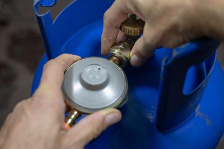 Regulador para bombona de gas propano-butano y accesorios sobre mesa de taller de madera. Accesorios de gas en el taller. Fondo oscuro.