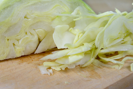 Fresh white cabbage cut into strips on the kitchen table. Vegetables prepared for salad. Light background.