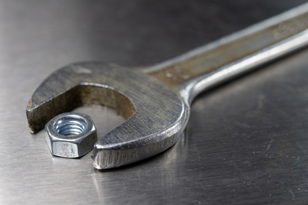 Wrench and nuts on a metal table in a workshop. Accessories for mechaics for minor mechanical repairs. Light background.