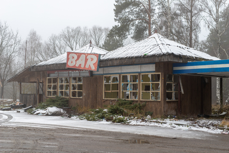 An old abandoned bar on a busy road. Ruin of restaurants in Central Europe. Season-winter