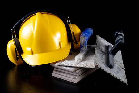 Tools for laying tiles and a helmet on a black table. Accessories for construction workers. Dark background.