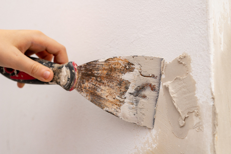 Applying putty to the wall in a new apartment. Renovation and painting of walls at home. Place - home farm. Фото со стока