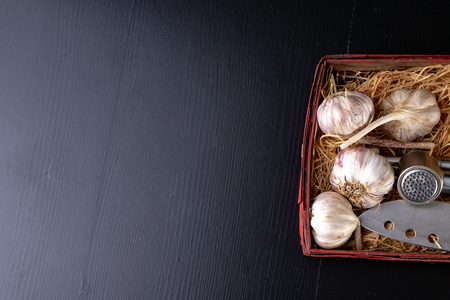 Fresh and healthy garlic on a black kitchen table. A healthy natural antibiotic for colds. Dark background. Фото со стока