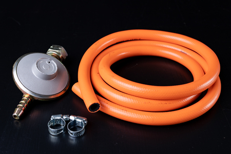Regulator for propane-butane gas cylinder and accessories on a wooden workshop table. Gas accessories in the workshop. Stock Photo