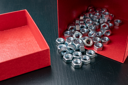 New nickel-plated screws in a red container. Accessories for mechanics on a wooden table. Dark background.