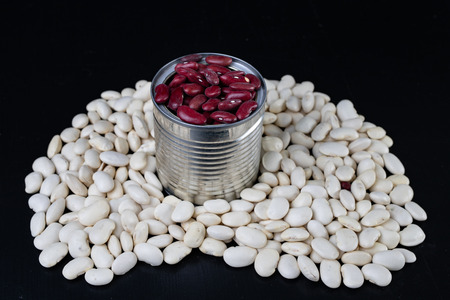 Tasty bean in a metal can on a wooden table. Products for preparing meals. Dark background.