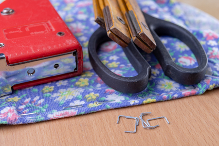Tacker and Staples used to upholster furniture. Accessories for employees in the carpentry shop. Light background