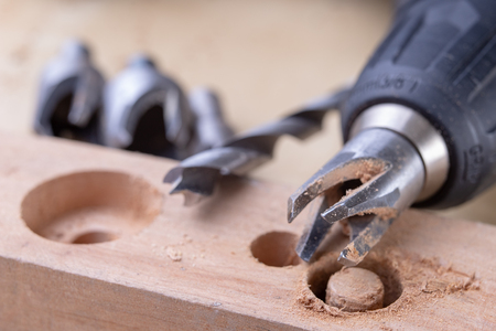 Drilling holes in the carpentry workshop with a special drill. Joinery accessories for repair work. Light background.