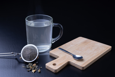 Brewing tea on a black table. Mug with a warm drink. Dark background. 免版税图像