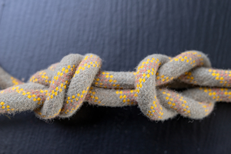 A knot tied on a sailing line. A rope for sailors and travelers on the table. Dark background. Banque d'images
