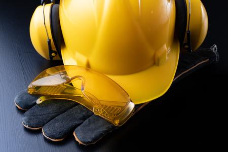 Helm und Zubehör für Bauarbeiter. Benötigtes Zubehör für die Arbeit auf der Baustelle. Dunkler Hintergrund. Standard-Bild