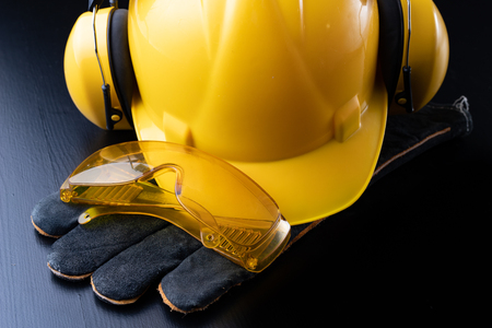 Helmet and accessories for construction workers. Accessories needed for work on the construction site. Dark background.