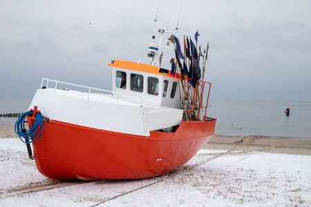 Fishing boats stretched out to the sea. Fishing port in Central Europe. Season winter.