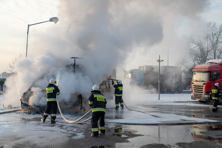 Car fire at the gas station. Burning van and firefighters extinguishing a fire. Season - winter. Editorial