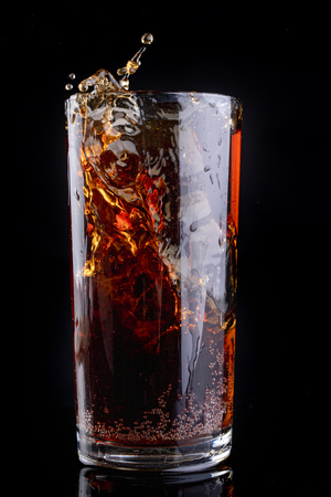 Dropping ice into a glass with a cold drink. Splash of drink in the bar. Dark background.