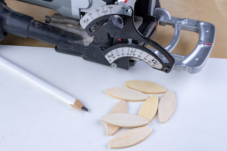 Joinery works in the workshop using sipes and a special milling machine. Light background.