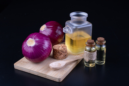 Onions and medicinal juice for colds. Home remedies for colds. Dark background. Imagens