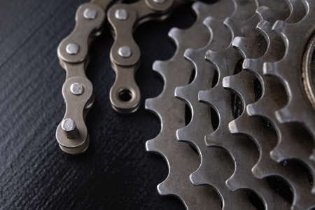 A gear and chain on a workshop table. Oiling and repair of bicycle drive. Dark background.