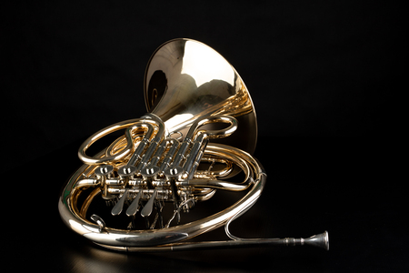 French horn on a wooden table. Beautiful polished musical instrument. Dark background. Imagens