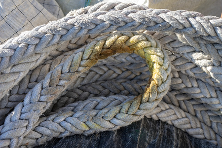 A rope lying on the wharf in the port. Fishing accessories in the port. Season winter. 免版税图像