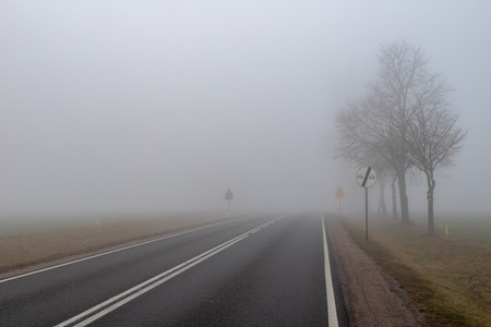 Asphalt road in a big fog. Low visibility on a busy road in Central Europe. Season of the spring. Banque d'images