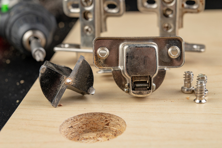 Milling the hole for the can hinge. Joinery works when assembling chipboard furniture. light background. Stok Fotoğraf