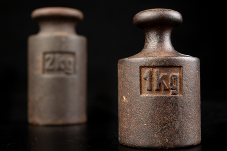 Old rusty metal weights for weighing products. Accessories for weight determination. Dark background.
