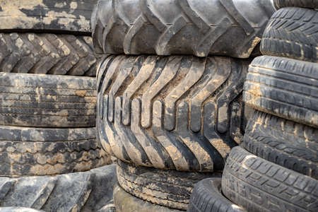 Old worn out tires on an abandoned trash dump. Garbage heap ready for disposal. Season of the spring.