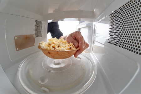 Microwave and bowl filled with popcorn. Device for heating dishes with the use of myocual waves. Light background. Imagens