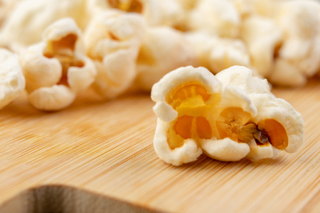 Popcorn on the kitchen table. Delicious roasted corn kernels. Light background.