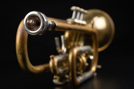 Old coated patina trumpet on a dark table. An inedible musical instrument. Dark background.