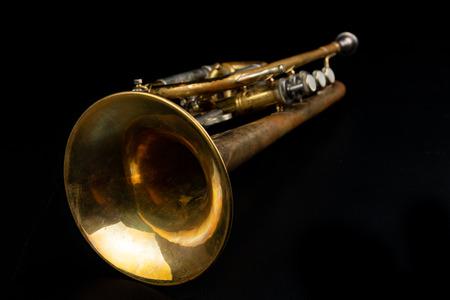 Trompeta de pátina revestida antigua sobre una mesa oscura. Un instrumento musical no comestible. Fondo oscuro.