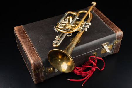 Old covered patina trumpet in a case. A historic wind musical instrument and a suitcase. Dark background.