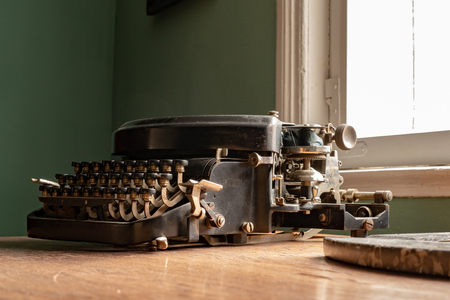 An old typewriter on a desk in a household. Accessories for writers in the comfort of your home. Dark background.